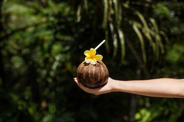 女性の手は、黄色の花とココナッツの飲み物を保持します