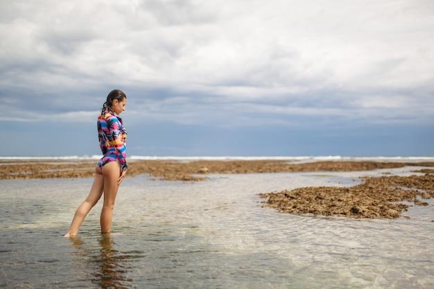 セクシーな女性がオーシャンビーチでポーズ