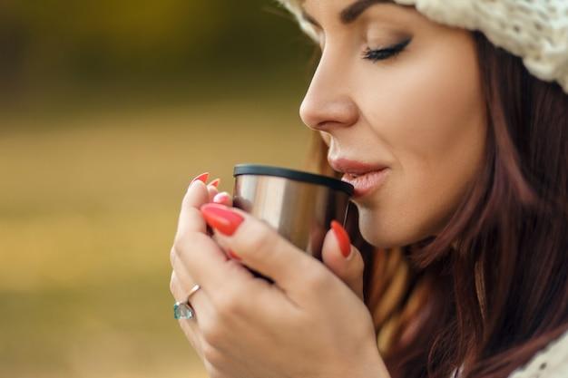 Шикарная женщина в шляпе наслаждается горячим кофе из термоса в холодном осеннем парке
