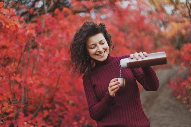 赤いセーターの女の子は魔法瓶からお茶を注ぐ