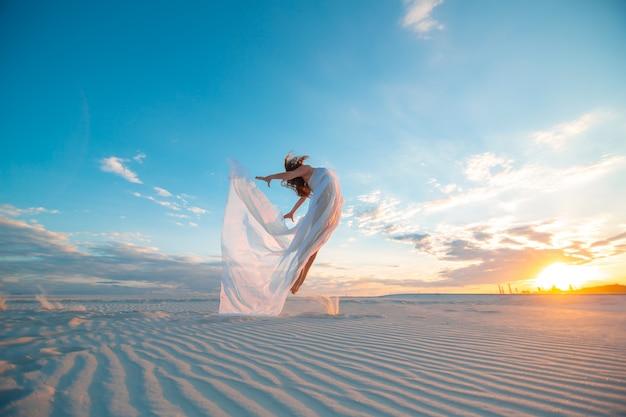 夕暮れの砂の砂漠で白いドレスを着た少女が踊りポーズをとる