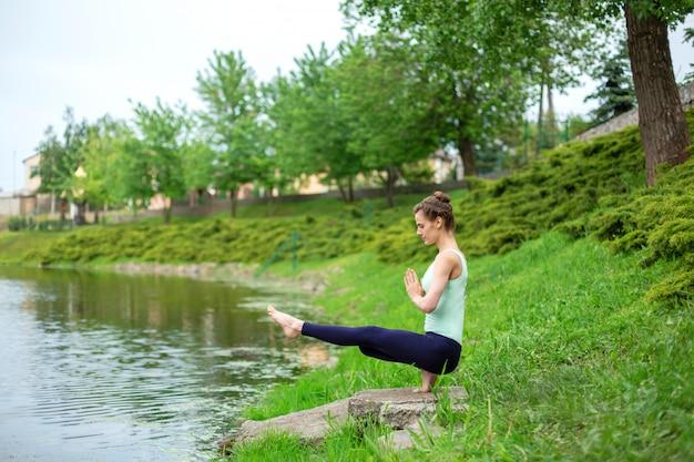 湖のそばの緑の芝生で夏にヨガをやっているスリムなブルネットの少女