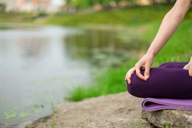 Худенькая брюнетка занимается спортом и выполняет красивые и сложные позы йоги в летнем парке. зеленый пышный лес и река женщина делает упражнения на коврик для йоги