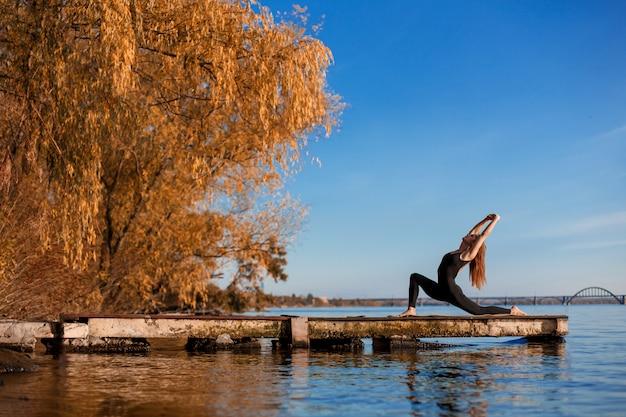 Молодая женщина практикующих йогу упражнения на тихой деревянной пристани с городом спорт и отдых в суете города