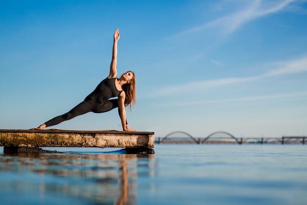 都市の静かな木製の桟橋でヨガの練習を練習する若い女性