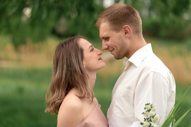 若いカップルがハグと踊る緑の草の芝生を愛しています。美しく幸せな女と男は優しくお互いに触れます。愛の美しいカップル。ドレスの少女とシャツの男