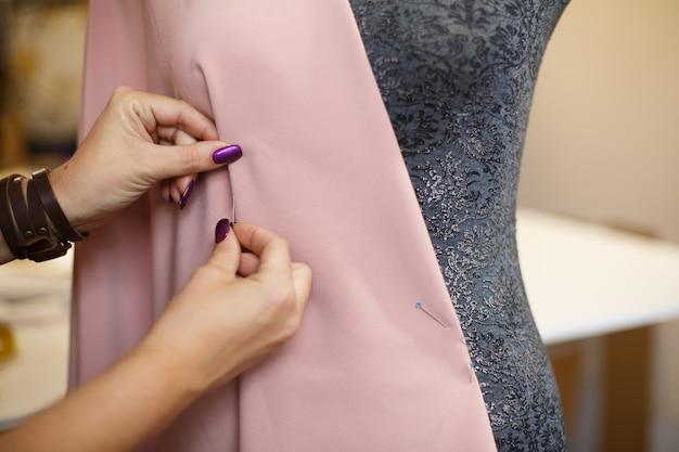 女性のドレスメーカーは、針で生地をマネキンに取り付けます。ドレスのデザインを作成します。テーラー産業