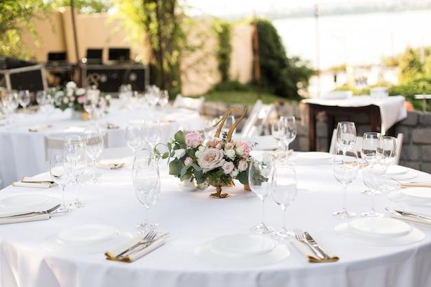 真ちゅう製の花瓶に生花で飾られた結婚式のテーブルセッティング。結婚式のフローリストリー。緑の自然の景色を望む屋外のゲスト用の宴会テーブル。バラ、トルコギキョウ、ユーカリの葉の花束。