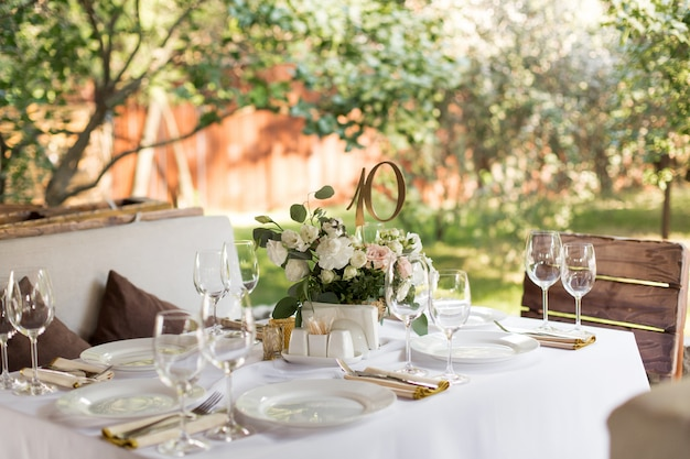 Сервировка свадебного стола украшена живыми цветами в латунной вазе. свадебная флористика. банкетный стол для гостей на свежем воздухе с видом на зеленую природу. букет из роз, эустомы и листьев эвкалипта.