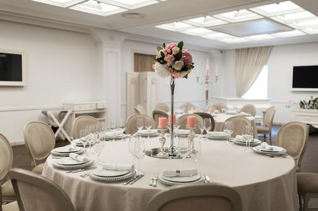 レストランの白いテーブルには生花が飾られています。スタイリッシュなイベント装飾。