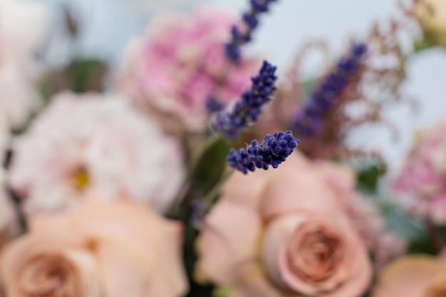 ピンクのバラが付いた新鮮なラベンダーのいくつかの枝。新鮮な花のイベント装飾