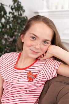 美しい赤毛の十代の少女の肖像画。ソファに座って、笑顔でカメラ目線のかわいい女の子
