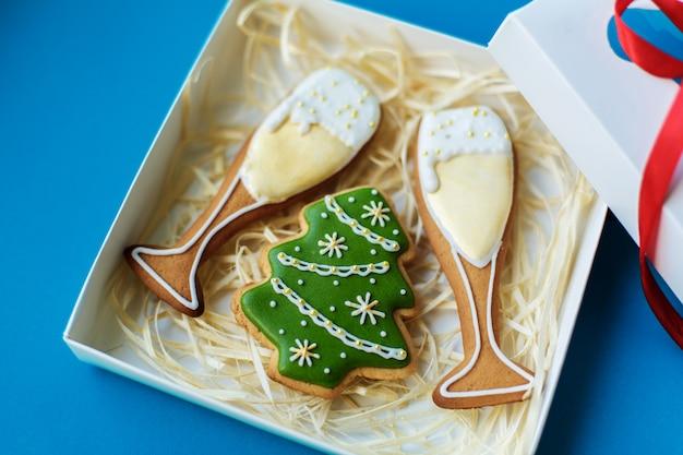 クリスマス正月休み、キャンパーグラス、クリスマスツリーのジンジャーブレッドは、青色の背景の休日のボックスに詰め