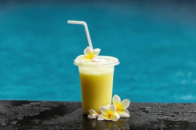 Фруктовый коктейль и цветок франжипани рядом с бассейном.