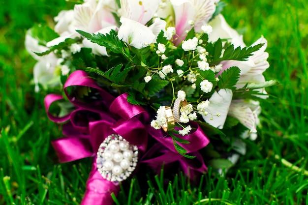 緑の芝生の上の結婚式の花のピンクホワイトブーケ