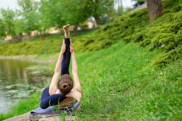 Худенькая брюнетка занимается спортом и выполняет красивые и сложные позы йоги в летнем парке. зеленый пышный лес и речка. женщина делает упражнения на коврик для йоги