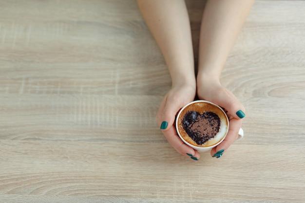 白いコーヒーカップを両手トップビュー。コーヒーにハートプリント
