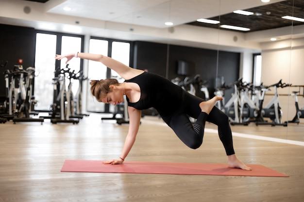 Девушка в спортзале занимается йогой, чтобы держать себя в форме или контролировать лишний вес.