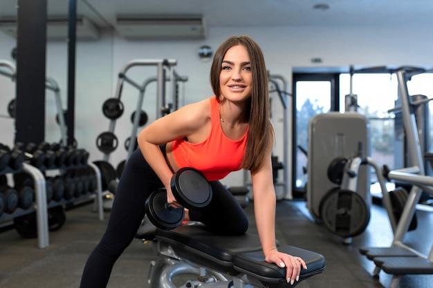 Портрет красивой подходящей женщины, подъем гантели на скамейке в тренажерном зале