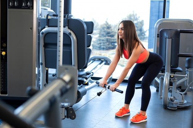 ブロックシミュレーターでの演習。上腕二頭筋の拡張。ジムでの運動の女性トレーニング