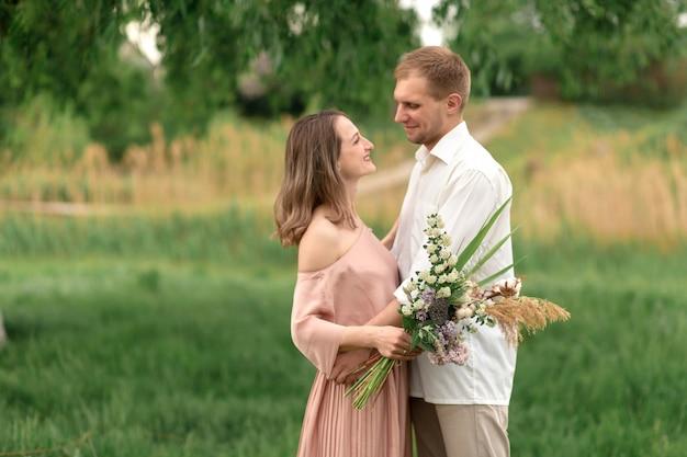 若いカップルがハグし、芝生の緑の草の上で踊って愛しています。美しく幸せな女と男は優しく触れ合う。愛の美しいカップル。ドレスの少女とシャツの男