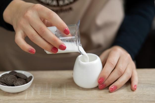 エプロンのバリスタはカップにミルクを注ぎます。コーヒーショップで働くバリスタ