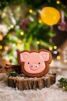 休日の伝統的な食べ物ベーカリー。ガーランドライトと居心地の良い暖かい装飾のジンジャーブレッドピンク豚頭
