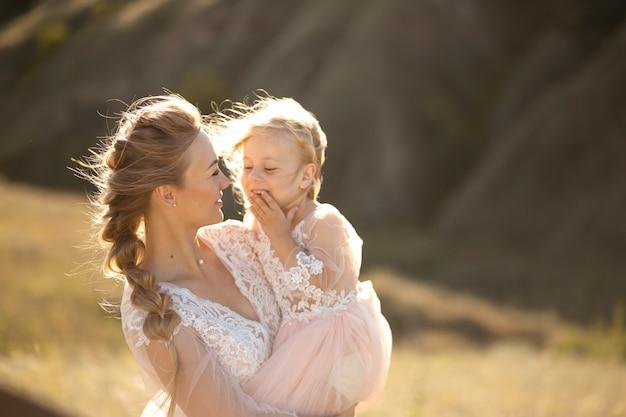 Портрет красивой молодой мамы держит ее любимую дочь на руках. родительская любовь, маленькая принцесса