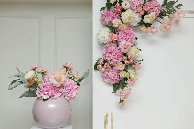 Свадебные украшения. праздничное оформление вазы живыми цветами возле свадебной арки. розовые розы и гвоздики