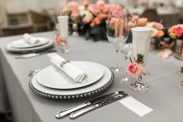 プレートとカトラリーを備えたスタイリッシュなテーブルセッティングの一部。近くに白い名刺があります。コピースペース