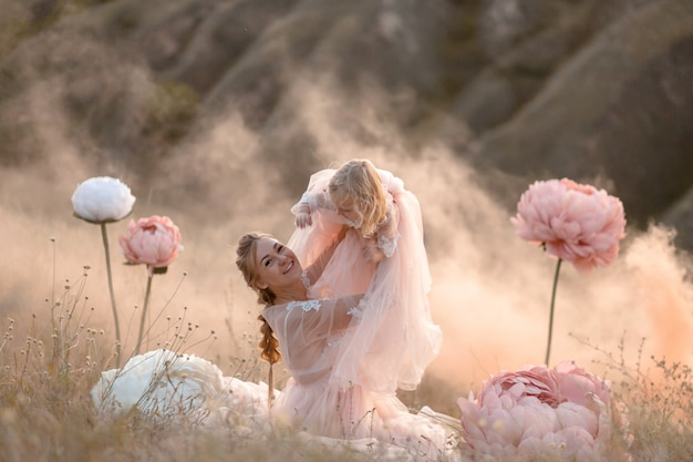 Мама и дочка в розовых сказочных платьях играют на поле в окружении больших розовых декоративных цветов