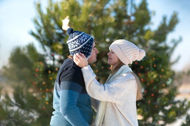 Парень с девушкой целуется на фоне зеленой елки, украшенной праздничными игрушками и гирляндами, зимой в лесу