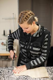 服の若い女の子デザイナー、彼のワークショップで服を作成するためにパターンで生地をカット