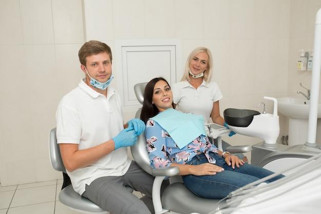 若い男性歯科医と幸せな女性患者。歯科医のオフィスライフスタイルシーン。医師の練習。患者の健康管理