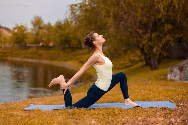 Стройная брюнетка занимается спортом и выполняет позы йоги осенью на природе у озера