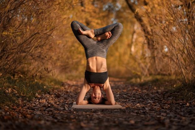 Тренировка йоги молодой женщины практикуя на парке осени с желтыми листьями. спортивно-оздоровительный образ жизни