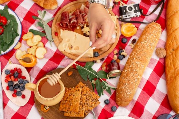 Женщина капает мед на бутерброд с пармой и сыром на открытом пикнике