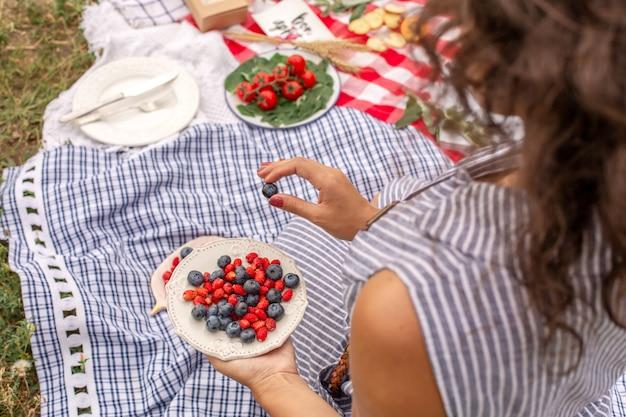 市松模様のスタイリッシュなドレスを着た女性は、ベリープレートからベリーを取る。屋外ピクニック