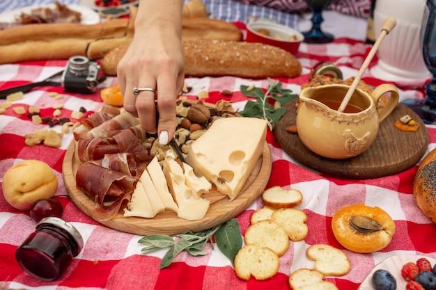 夏の屋外ピクニックパーティー。市松模様の毛布の上に食べ物、蜂蜜、果物が置かれていました。