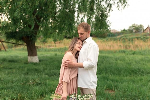 Молодая влюбленная пара обниматься и танцевать на зеленой траве на лужайке