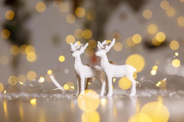 クリスマスをテーマにした装飾の置物。クリスマスの鹿。クリスマスツリーの装飾。お祝いの装飾、温かみのあるボケライト。