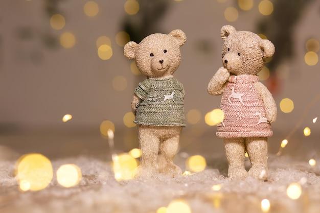 Декоративные фигурки на рождественскую тему. статуэтки милых плюшевых мишек мальчика и девочки в свитерах с оленями. праздничный декор, теплые огни боке.