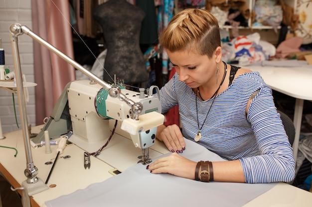 若い女性の金髪洋裁布デザイナーがミシンで動作します
