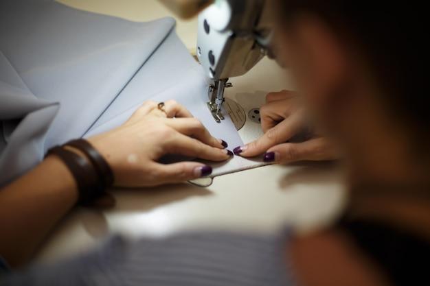 職場の仕立て屋。仕立て産業。女の子はミシンで縫います。工場服