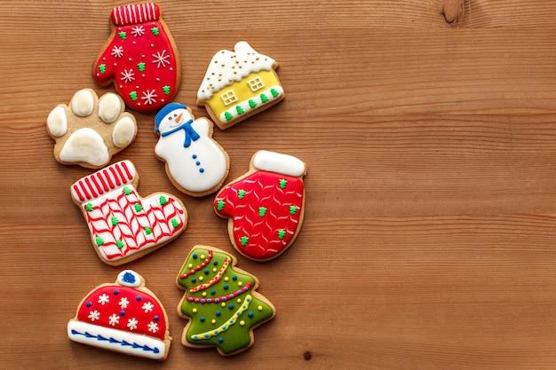 クリスマス正月休日背景、カラフルなジンジャーブレッドクッキー、木製のテーブルのコーン。コピースペース。休日の概念。