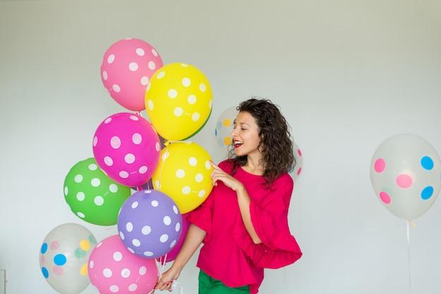 色の風船を持つ美しいかわいい陽気な女の子。休日お誕生日おめでとう。