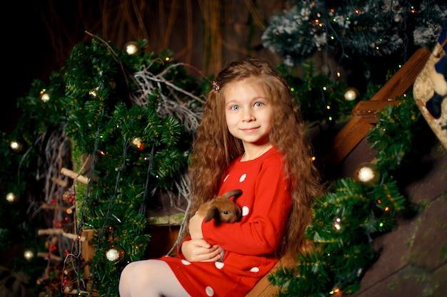 Портрет милая маленькая девочка держит кролика в ее руках. рождественское украшение. концепция праздников
