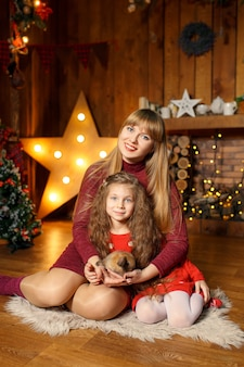 母と娘のかわいいウサギと床に座っての家族写真。クリスマスの飾り