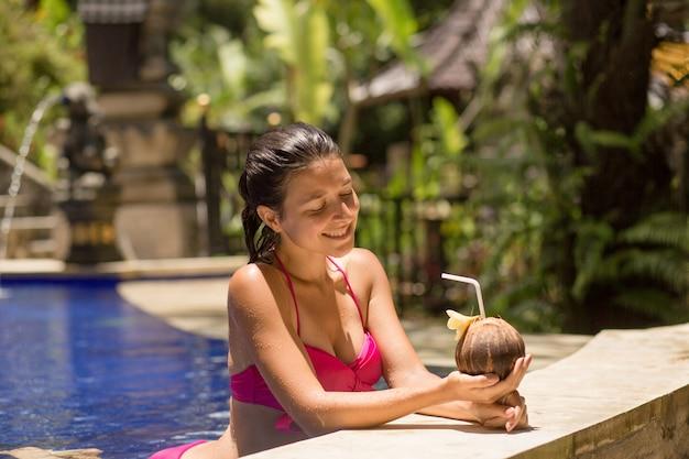 Сексуальная молодая женщина в розовом купальнике с кокосовым напитком в бассейне на отдыхе.