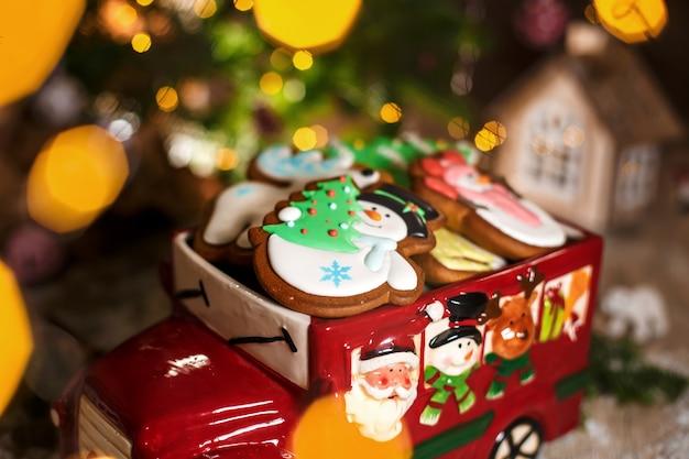 休日の伝統的な食べ物ベーカリー。ガーランドライトと居心地の良い暖かい装飾でクリスマスジンジャーブレッドケーキと装飾的なおもちゃの車